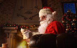 Portrait of happy Santa Claus sitting at his room at home near Christmas tree and reading Christmas letter or wish list. Portrait of happy Santa Claus sitting Royalty Free Stock Photos