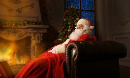 Portrait of happy Santa Claus sitting at his room at home near Christmas tree and reading Christmas letter or wish list. Portrait of happy Santa Claus sitting Royalty Free Stock Images
