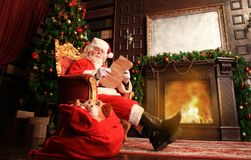Portrait of happy Santa Claus sitting at his room at home near Christmas tree and reading Christmas letter or wish list. Portrait of happy Santa Claus sitting