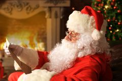 Portrait of happy Santa Claus sitting at his room at home near Christmas tree and reading Christmas letter or wish list. Royalty Free Stock Photo
