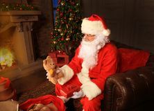 Portrait of happy Santa Claus sitting at his room at home near Christmas tree and reading Christmas letter or wish list. Portrait of happy Santa Claus sitting Stock Image