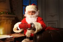 Portrait of happy Santa Claus sitting at his room at home near Christmas tree and reading Christmas letter or wish list. Portrait of happy Santa Claus sitting Stock Photography