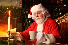 Portrait of happy Santa Claus sitting at his room at home near Christmas tree and reading Christmas letter or wish list. stock images