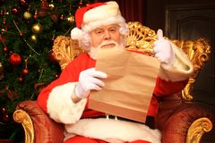 Portrait of happy Santa Claus sitting at his room at home near Christmas tree and reading Christmas letter or wish list. royalty free stock photography