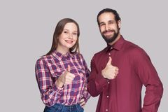 Portrait of happy satisfied bearded man and woman in casual style standing and looking at camera, smiling with thumbs up. stock photo
