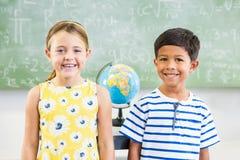 Portrait of happy school kids standing in classroom stock image