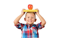 Portrait of happy schoolboy with book and apple on his head isolated white background. Education Royalty Free Stock Photography