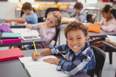 Portrait of happy schoolboy doing his homework in classroom. At school Royalty Free Stock Image