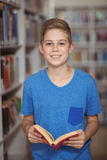 Portrait of happy schoolboy holding book in library. At school Stock Photos