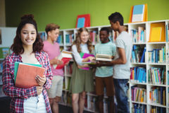 Portrait of happy schoolboy holding book in library. At school Royalty Free Stock Photo