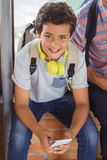 Portrait of happy schoolboy sitting on window sill and using mobile phone in corridor Royalty Free Stock Photo