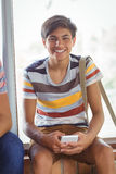 Portrait of happy schoolboy sitting on window sill and using mobile phone in corridor Stock Photo
