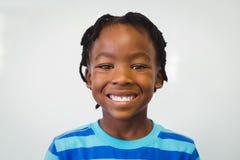 Portrait of happy schoolboy smiling in classroom Stock Image