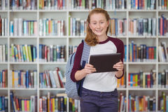 Portrait of happy schoolgirl holding digital tablet in library Royalty Free Stock Photo