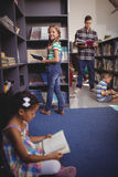 Portrait of happy schoolgirl selecting book from bookshelf in library. At school Royalty Free Stock Images
