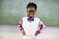 Portrait of happy schoolgirl standing with hand on hip. In classroom Royalty Free Stock Photography