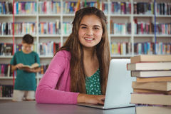 Portrait of happy schoolgirl using laptop in library Royalty Free Stock Images