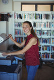 Portrait of happy schoolgirl using Xerox photocopier in library. At school Stock Images