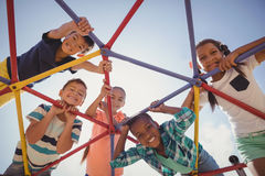 Portrait of happy schoolkids looking through dome climber Royalty Free Stock Photography