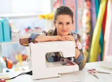 Portrait of happy seamstress with sewing machine Royalty Free Stock Image