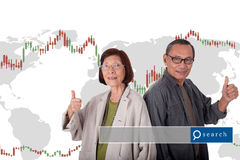 Portrait of happy senior asian couples on world map ans stock ma. Rket chart background with search engine graphics Stock Photography