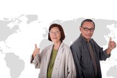 Portrait of happy senior asian couples on world map background Stock Photo