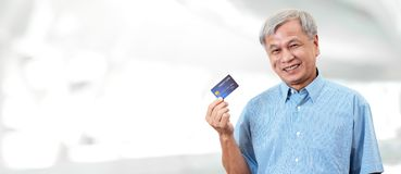 Portrait of happy senior asian man holding credit card and showing on hand smiling and looking at camera on isolated blurred stock image