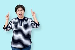 Portrait of happy senior asian woman gesture or pointing hand and finger up and looking at camera on isolated background feeling stock images