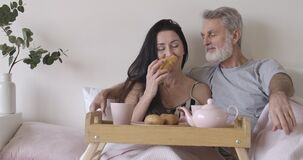 Portrait of happy senior Caucasian couple talking and smelling fresh croissant. Positive mature man and woman having