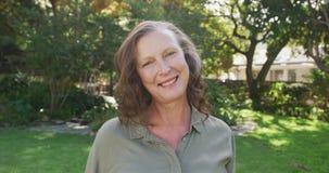 Portrait of happy senior caucasian woman standing in garden smiling
