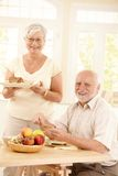 Portrait of happy senior couple at breakfast Stock Photography
