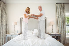 Portrait of happy senior couple dancing on bed Royalty Free Stock Photo