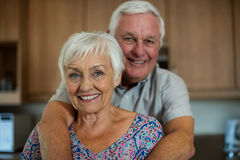 Portrait of happy senior couple embracing each other in kitchen Stock Photography
