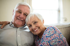 Portrait of happy senior couple embracing each other in living room Stock Images