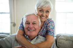 Portrait of happy senior couple embracing each other in living room Stock Image