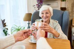 Senior Couple Exchanging Gifts. Portrait of happy senior couple exchanging gifts sitting at dinner table, focus on happy senior women receiving gift box Royalty Free Stock Images