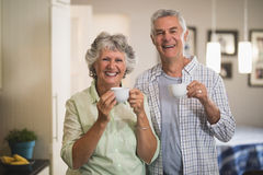 Portrait of happy senior couple holding cups in kitchen Royalty Free Stock Images