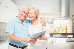 Portrait of happy senior couple holding digital tablet in kitchen Royalty Free Stock Image