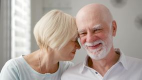 Portrait of happy senior couple at home. Senior man expresses his emotions and kisses his wife