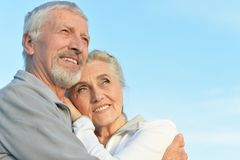 Portrait of happy senior couple hugging against blue sky stock photography