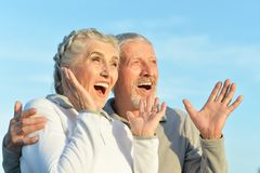 Portrait of happy senior couple hugging against blue sky royalty free stock images