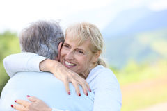 Portrait of happy senior couple hugging outdoors Royalty Free Stock Images