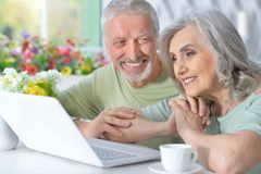 Portrait of happy senior couple with laptop at home stock photo