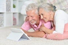 Portrait of happy senior couple lying on floor royalty free stock photo
