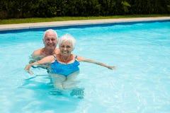 Portrait of happy senior couple in the pool Stock Photo