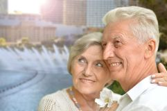 Portrait of happy senior couple posing against blurred cityscape background royalty free stock images