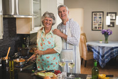 Portrait of happy senior couple preparing food together in kitchen Royalty Free Stock Photography