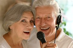 Senior couple singing karaoke. Portrait of happy senior couple singing karaoke Royalty Free Stock Photos
