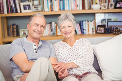 Portrait of happy senior couple sitting in living room Royalty Free Stock Photos