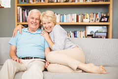 Portrait of happy senior couple sitting on sofa against bookshelf Royalty Free Stock Photo